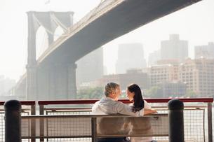 Couple relaxing on bench under Brooklyn Bridgeの写真素材 [FYI03630183]