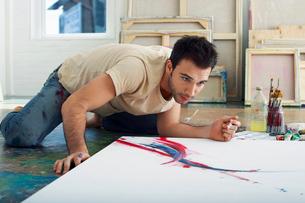 Artist painting on canvas on studio floorの写真素材 [FYI03630206]
