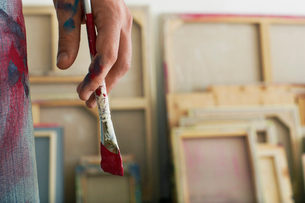 Artist holding paint brush  standing in studio  close up oの写真素材 [FYI03630210]