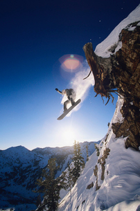 Snowboarder jumping from mountain ledgeの写真素材 [FYI03630233]