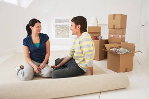 Couple sitting on half-rolled carpet in new homeの写真素材 [FYI03630553]
