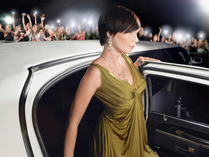 Woman in evening wear getting out of limousine in front ofの写真素材 [FYI03630587]