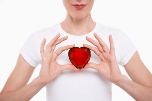 Woman in white t-shirt holding red glass heart in both hanの写真素材 [FYI03630593]