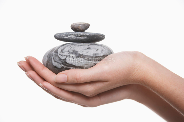 Woman holding pile of stones  close-up on handsの写真素材 [FYI03630596]
