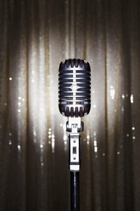 Old fashioned microphone in front of stage curtainの写真素材 [FYI03630702]