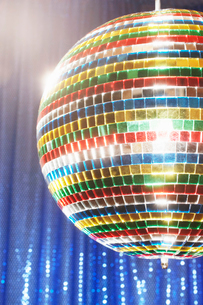 Multi-coloured disco ball in front of blue stage curtainの写真素材 [FYI03630712]