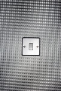 Silver light switch on wallpaper covered wallの写真素材 [FYI03630719]