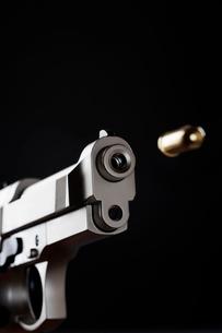 Gun shooting bullet on black background  close upの写真素材 [FYI03630723]