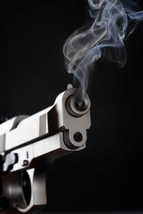Smoking Handgun against black backgroundの写真素材 [FYI03630725]