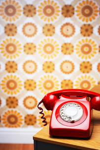 Old fashioned red telephone on table in front of flowery wの写真素材 [FYI03630731]