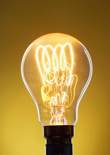 Illuminated light bulb against yellow background in studioの写真素材 [FYI03630742]