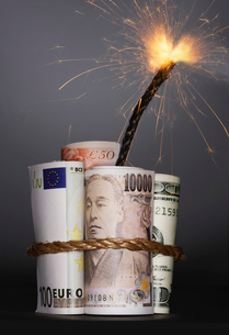 Rolls of money symbolizing dynamite with lit fuse  in studの写真素材 [FYI03630754]