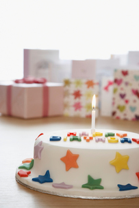 Decorated birthday cake with candle in front of cards in sの写真素材 [FYI03630756]