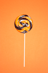 Black and orange lollypop on orange backgroundの写真素材 [FYI03630760]