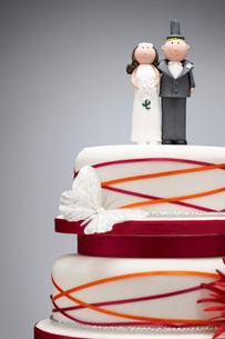 Comical bride and groom figurines on top of wedding cakeの写真素材 [FYI03630762]