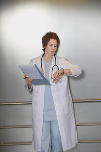 Physician Checking Wristwatch in elevatorの写真素材 [FYI03630837]
