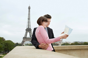 France  Paris  Couple reading map on balcony in front of Eの写真素材 [FYI03630975]