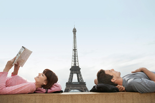 Couple lying on ledge of the Trocadero with Eiffel Tower vの写真素材 [FYI03630979]