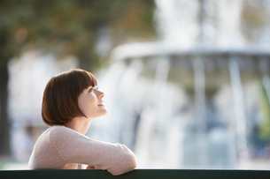 Young woman sitting on bench in front of fountain  head anの写真素材 [FYI03630981]
