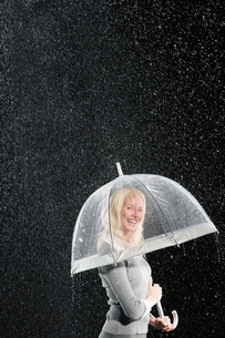 Smiling businesswoman Standing Under Umbrella during rainの写真素材 [FYI03631009]