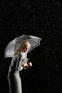 Businesswoman hunching down Under Umbrella for protectionの写真素材 [FYI03631010]