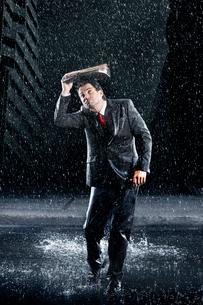 Businessman covering head with binder  running through raiの写真素材 [FYI03631017]