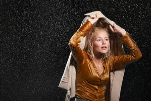Businesswoman covering head with jacket during rainstormの写真素材 [FYI03631018]