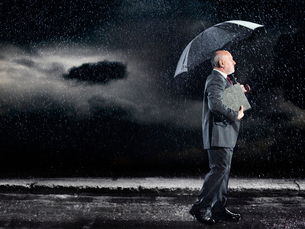 Businessman Walking in rain under umbrella  side viewの写真素材 [FYI03631019]