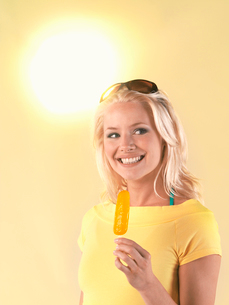 Woman holding popsicle on hot Summer Dayの写真素材 [FYI03631034]