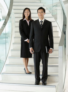 Confident Businesspeople standing on staircaseの写真素材 [FYI03631044]
