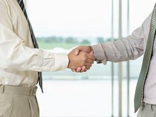 Businessmen Shaking Hands in front of window  side view  cの写真素材 [FYI03631061]