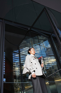 Woman Carrying Notebooks  standing outside  low angle viewの写真素材 [FYI03631068]