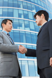 Businessmen Shaking Hands outside office building  low angの写真素材 [FYI03631089]