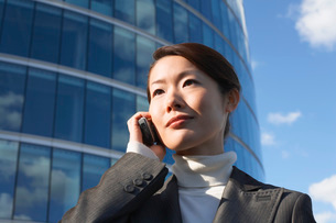 Businesswoman standing outside office building  Using Cellの写真素材 [FYI03631090]