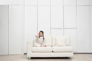 Young  barefoot Girl sitting cross-legged Sofaの写真素材 [FYI03631093]