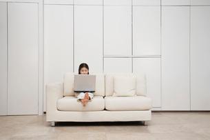 Young  barefoot Girl Using Laptop on Sofaの写真素材 [FYI03631094]