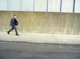 Teenager in suit walking on street  side viewの写真素材 [FYI03631105]