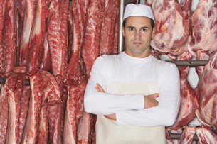 Butcher Standing  arms crossed  in front of raw meat  in Mの写真素材 [FYI03631128]