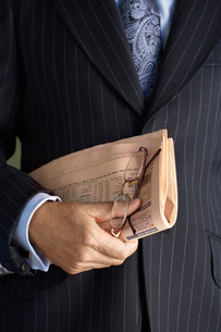 Middle-aged businessman in full suit  holding pair of glasの写真素材 [FYI03631187]