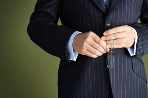 Middle-aged businessman in full suit  holding pair of glasの写真素材 [FYI03631190]