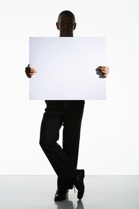 Silhouetted man standing  holding large blank cardの写真素材 [FYI03631192]