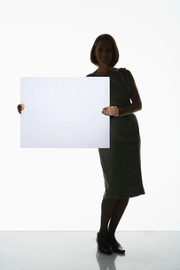 Silhouetted woman standing  holding large blank card to siの写真素材 [FYI03631194]
