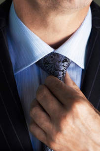 Middle-aged businessman in full suit  adjusting tie   midの写真素材 [FYI03631196]