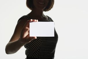 Smiling  silhouetted woman standing  holding large blank cの写真素材 [FYI03631199]