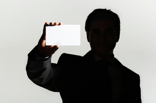 Silhouetted man standing  holding large blank cardの写真素材 [FYI03631203]