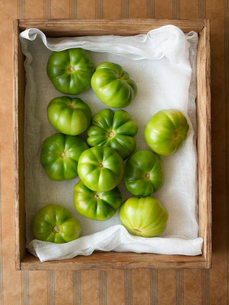 Green tomatoes in wooden box  overhead viewの写真素材 [FYI03631214]