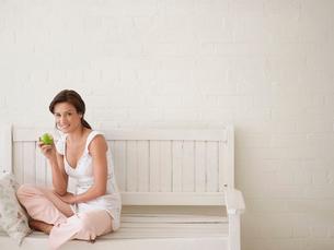 Woman Eating Apple  sitting  cross-legged on benchの写真素材 [FYI03631222]