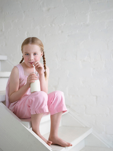 Barefoot Girl Drinking Glass of Milk  sitting on stairsの写真素材 [FYI03631223]