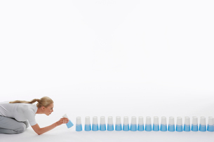 Woman lining up plastic cups on ground against white backgの写真素材 [FYI03631330]