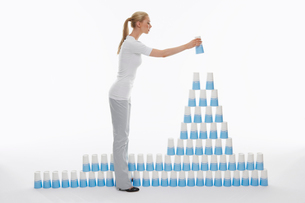 Woman stacking plastic cups into pyramid against white bacの写真素材 [FYI03631331]